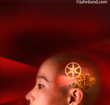 Picture of a bald Asian woman's head with the image of a movie projector showing through. Strange weird stock photos for conceptual uses. An abstract image.